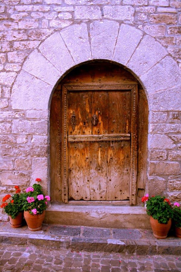Ημικυκλική είσοδος στο σπίτι πετρών, ξύλινη παλαιά πόρτα, λουλούδια στα δοχεία στοκ φωτογραφίες με δικαίωμα ελεύθερης χρήσης