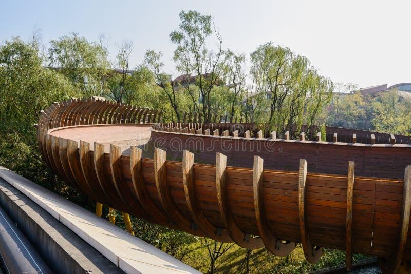 Ημισωληνοειδής ξύλινη γέφυρα για πεζούς στον αέρα το ηλιόλουστο χειμερινό μεσημέρι στοκ εικόνα