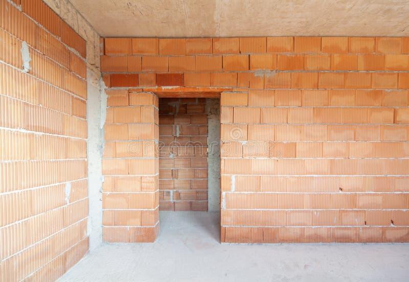 Ημιτελές εσωτερικό του κτιρίου υπό κατασκευή Τοίχοι με κόκκινο τούβλο Νέο σπίτι στοκ φωτογραφία