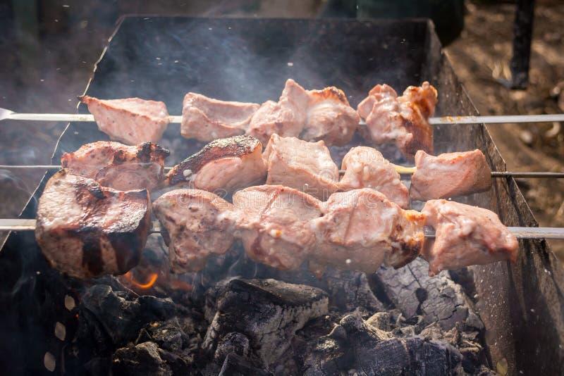 Ημιτελή οβελίδια κρέατος στη σχάρα στον καπνό στοκ φωτογραφίες
