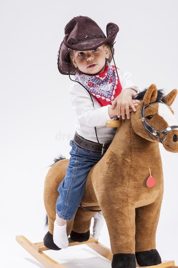 Ηρεμία και βέβαιος λίγο καυκάσιο κορίτσι στον ιματισμό Cowgirl στο συμβολικό άλογο στοκ εικόνες