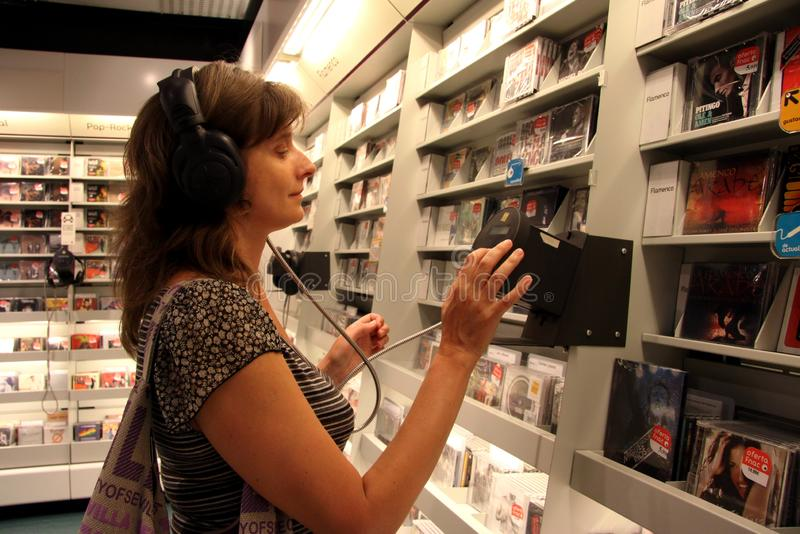 Η άγνωστη γυναίκα ακούει έναν δίσκο σε ένα κατάστημα μουσικής στη Σεβίλη στοκ εικόνα