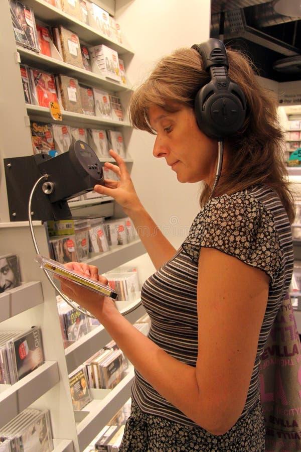 Η άγνωστη γυναίκα ακούει έναν δίσκο σε ένα κατάστημα μουσικής στη Σεβίλη στοκ εικόνες