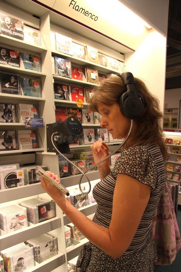 Η άγνωστη γυναίκα ακούει έναν δίσκο σε ένα κατάστημα μουσικής στη Σεβίλη στοκ φωτογραφία με δικαίωμα ελεύθερης χρήσης