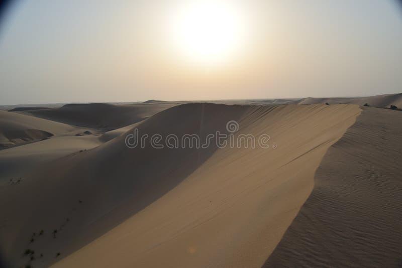 Η άμμος και ο ουρανός της αραβικής ερήμου ως ήλιο αρχίζουν να θέτουν στοκ εικόνα