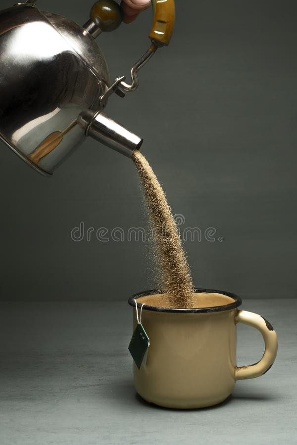 Η άμμος χύνει από teapot σε μια κούπα στοκ φωτογραφίες