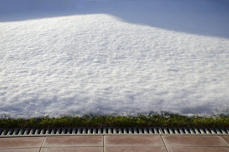 Η άνοιξη άρχισε, υποχωρώντας το χιόνι στον κήπο με την πράσινα χλόη και το πεζοδρόμιο στοκ φωτογραφία