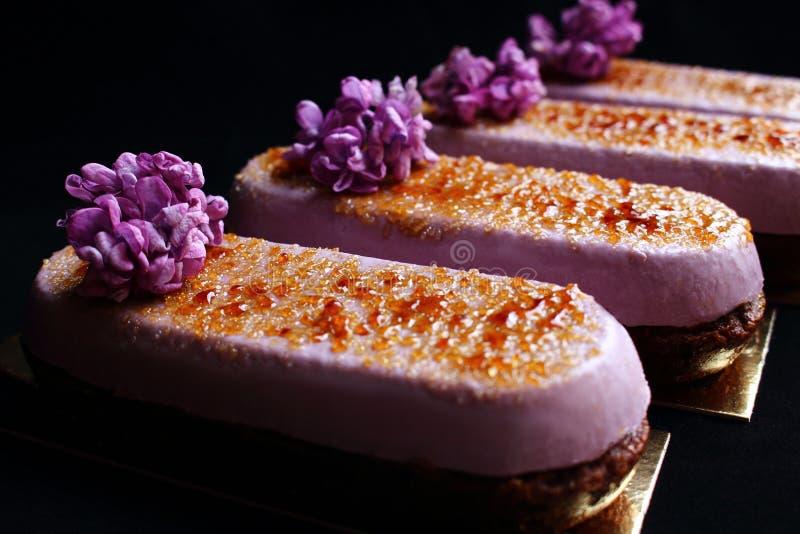 Η άνοιξη ανθίζει μη ψημένο creme brulle τα επιδόρπια με τα φρέσκα ιώδη λουλούδια και το κάλυμμα καραμέλας που απομονώνεται στο μα στοκ εικόνες