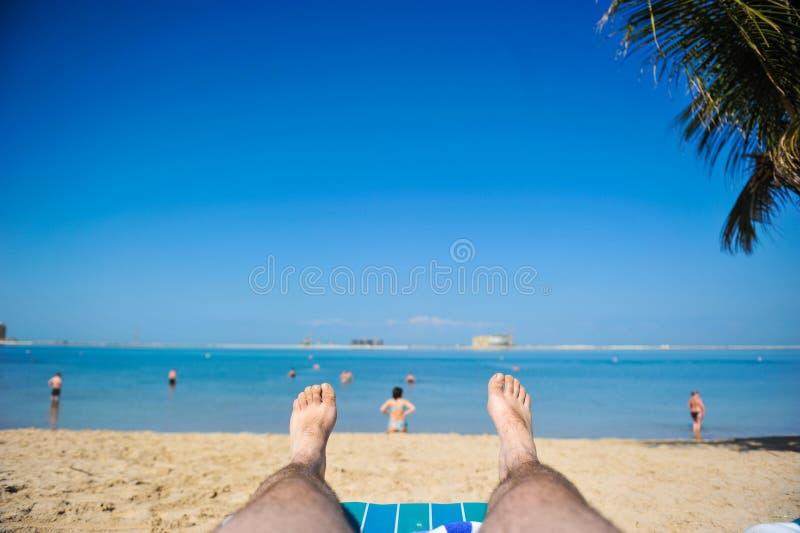 Η άποψη από τα μάτια ενός ατόμου που βρίσκεται στην άμμο και εξετάζει έξω τη θάλασσα και εσείς μπορεί να δει τα πόδια του στοκ εικόνα με δικαίωμα ελεύθερης χρήσης