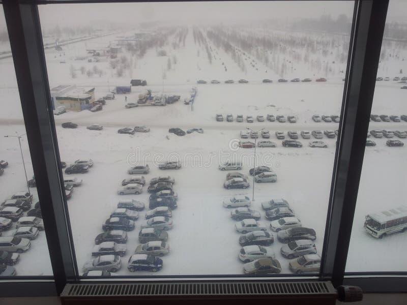 Η άποψη από το παράθυρο γραφείων στο χειμερινό χώρο στάθμευσης στοκ φωτογραφία