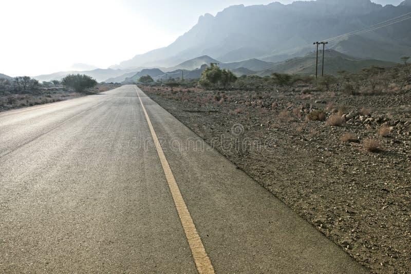 η άποψη ενός δρόμου που οδηγεί στο Jebel υποκρίνεται στα βουνά Hajar μέσα στοκ εικόνες