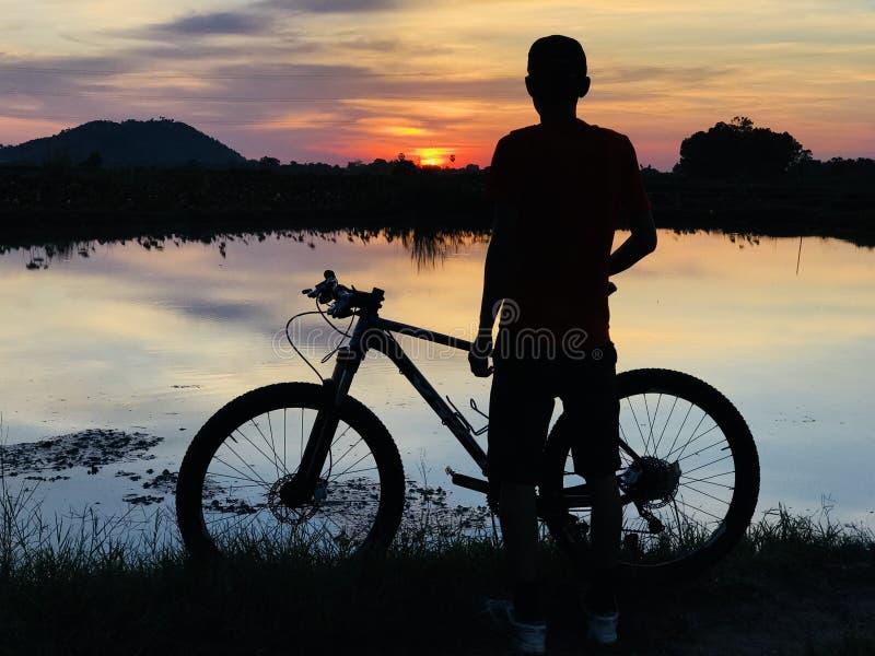 Η άποψη ηλιοβασιλέματος με τον ποδηλάτη στοκ εικόνα με δικαίωμα ελεύθερης χρήσης