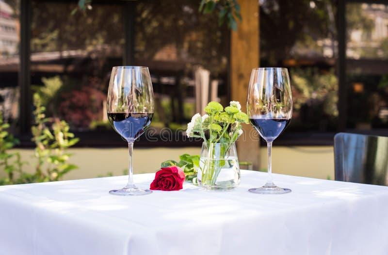 Η άποψη κινηματογραφήσεων σε πρώτο πλάνο όμορφου κόκκινου αυξήθηκε λουλούδι με το κρασί στον πίνακα στοκ εικόνα