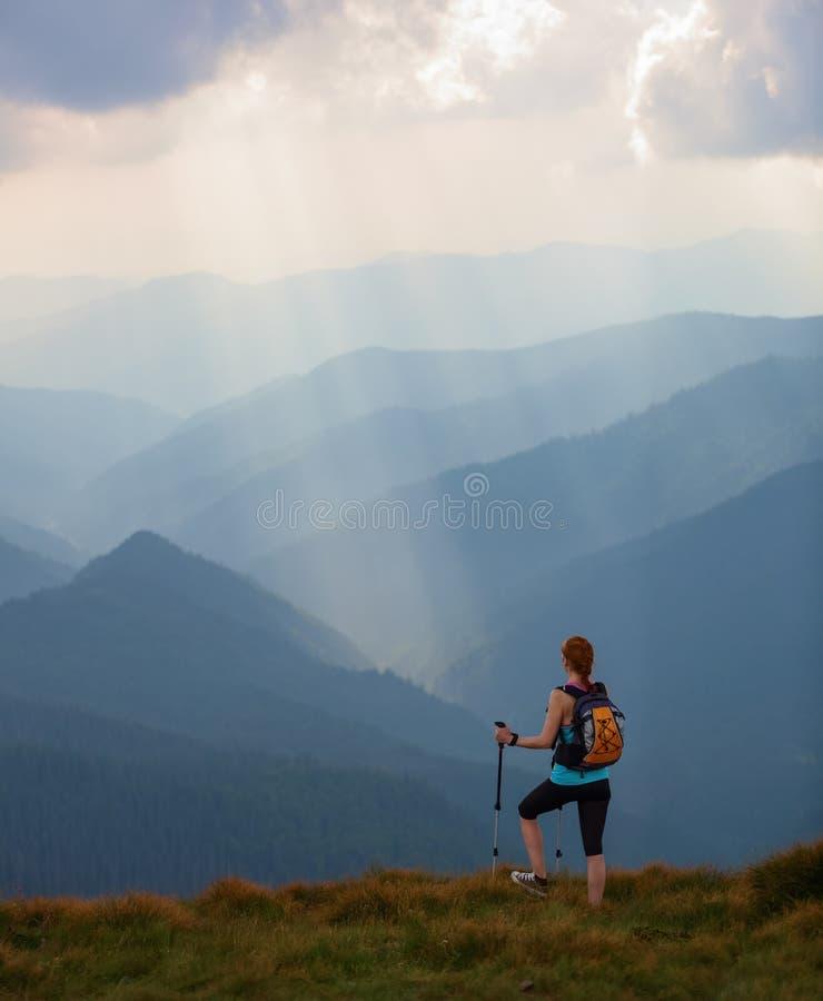 Η άποψη με τα υψηλά βουνά στην ομίχλη Οι ακτίνες ήλιων είναι διαφωτίζουν τα δάση Το ακραίο κορίτσι με τα ακολουθώντας ραβδιά στοκ φωτογραφία με δικαίωμα ελεύθερης χρήσης