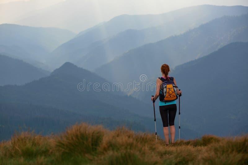 Η άποψη με τα υψηλά βουνά στην ομίχλη Οι ακτίνες ήλιων είναι διαφωτίζουν τα δάση Το ακραίο κορίτσι με τα ακολουθώντας ραβδιά στοκ εικόνες