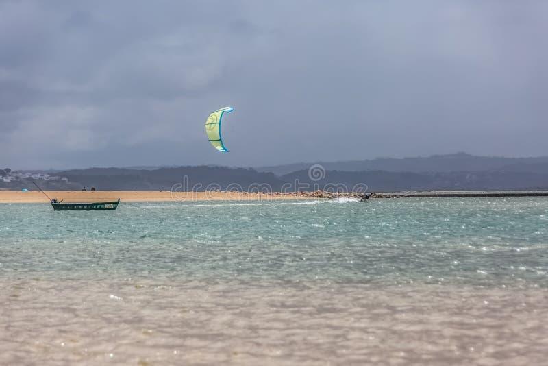 Η άποψη μιας επαγγελματικής φιλάθλου που ασκεί τον ακραίο αθλητισμό Kiteboarding στη λιμνοθάλασσα Obidos, Foz κάνει Arelho, Πορτο στοκ φωτογραφία