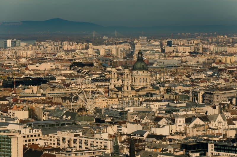 Η άποψη πέρα από τις στέγες του κέντρου της πόλης της Βουδαπέστης, η βασιλική του ST Stephen και τα ferris κυλούν στη μέση, Βουδα στοκ εικόνα