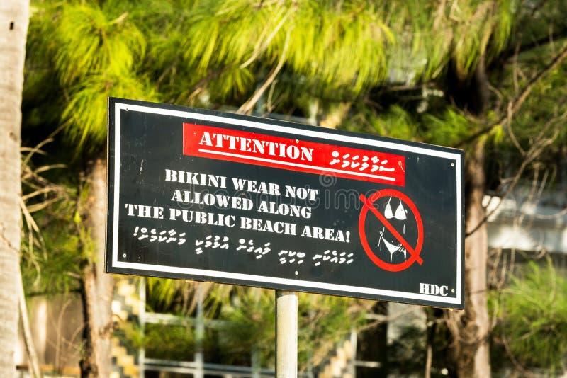 Η άποψη σχετικά με το μπικίνι σημαδιών ` που δεν επιτρέπεται πλησίον κατά μήκος της δημόσιας περιοχής `, αρσενικό παραλιών Μαλδίβ στοκ εικόνα με δικαίωμα ελεύθερης χρήσης