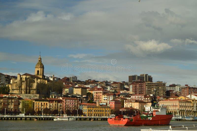 Η άποψη της εκκλησίας και τα κτήρια Porugalete στην ανατολή με μια βάρκα που διασχίζει τη Ria συλλαμβάνουν το τσοκ από Getxo Αρχι στοκ φωτογραφίες με δικαίωμα ελεύθερης χρήσης