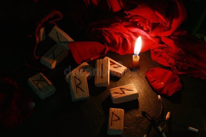 Η άποψη της μυστικής σύνθεσης των ξύλινων ρούνων γύρω από τα πέταλα των κόκκινων τριαντάφυλλων, ένα κερί καίει δίπλα σε το και τι στοκ εικόνα