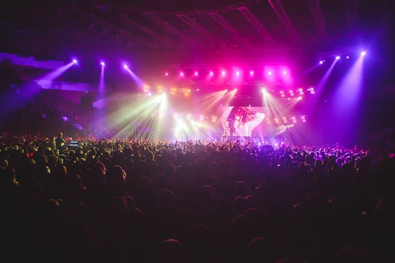 Η άποψη της συναυλίας βράχου παρουσιάζει στη μεγάλη αίθουσα συναυλιών, με το πλήθος και τα φω'τα σκηνών, μια συσσωρευμένη αίθουσα στοκ εικόνες