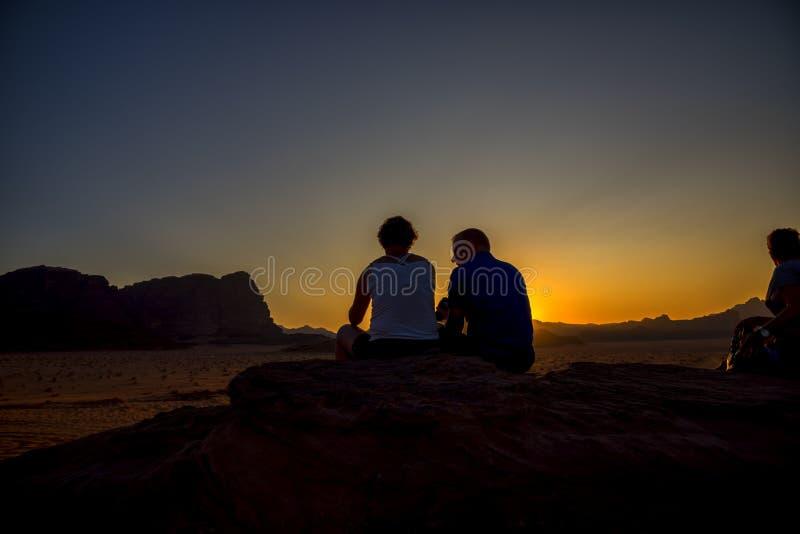 Η άποψη του ηλιοβασιλέματος στο ιορδανικό wadi-ρούμι ερήμων, όπου μερικοί άνθρωποι κάθονται σε μια μικρή προσοχή βουνών, και βλέπ στοκ φωτογραφία με δικαίωμα ελεύθερης χρήσης