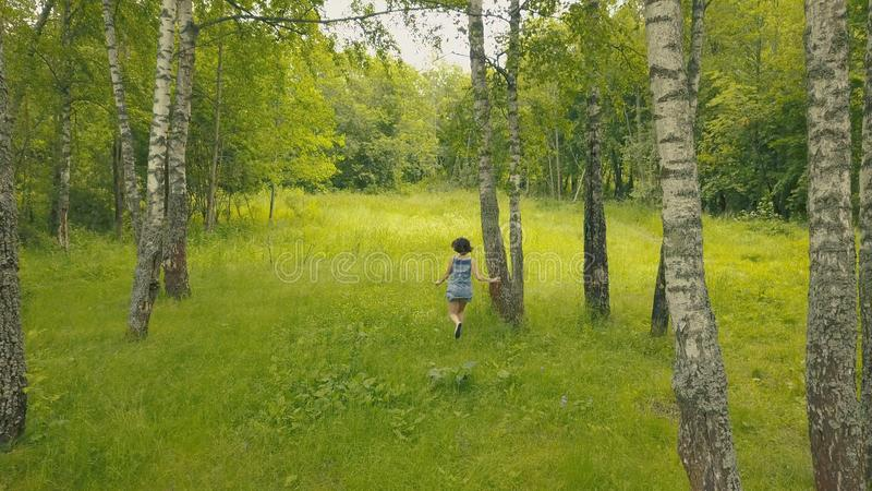 Η άποψη Arial που χαμογελά τη νέα γυναίκα στο δάσος με ακολουθεί στο δάσος στοκ εικόνα