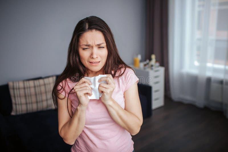 Η άρρωστη νέα στάση γυναικών στο δωμάτιο και θέλει να φτερνιστεί Συρρικνώνεται Άσπρος ιστός λαβής γυναικών στοκ φωτογραφία