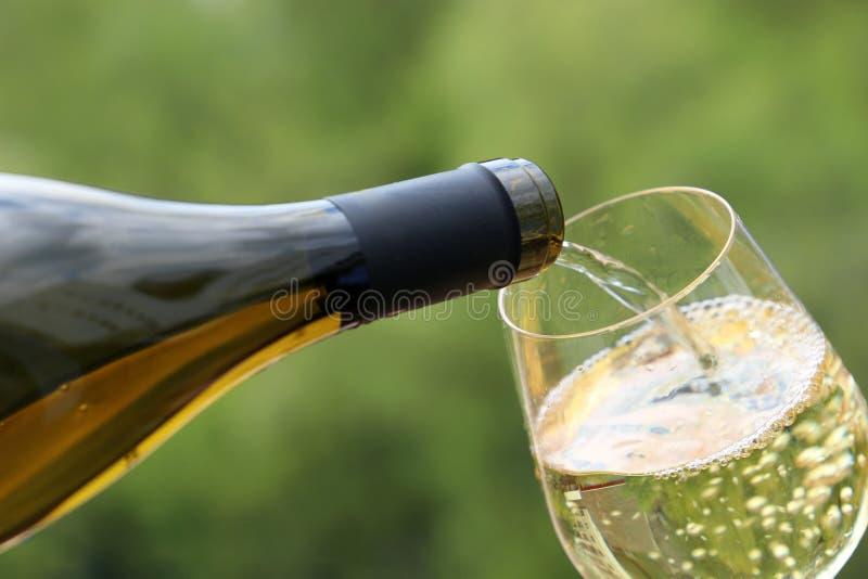 Η άσπρη έκχυση κρασιού από το μπουκάλι στο γυαλί στην πράσινη φύση θόλωσε το υπόβαθρο στοκ φωτογραφία