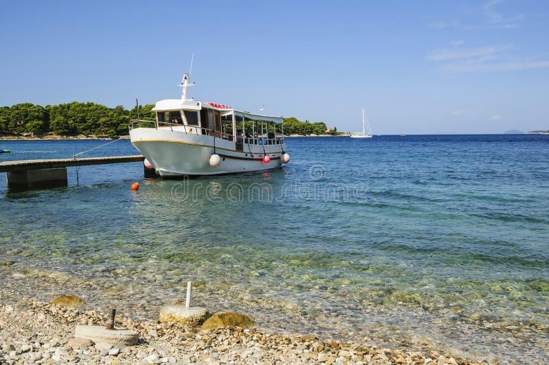 Η άσπρη βάρκα για τη μεταφορά των τουριστών, ταξιδιώτες και επιβάτες vacationers, έδεσε στην αποβάθρα αδριατική θάλασσα της Κρ&o στοκ φωτογραφία