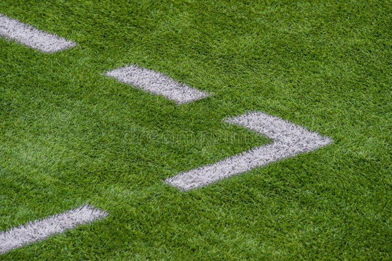 Η άσπρη γραμμή που χαρακτηρίζει στο τεχνητό πράσινο γήπεδο ποδοσφαίρου χλόης στοκ φωτογραφία