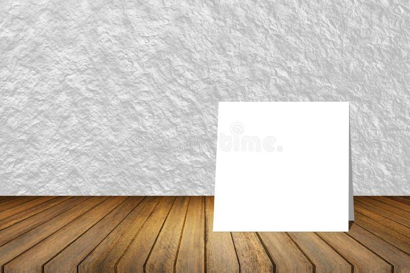 Η άσπρη κάρτα έβαλε στο ξύλινο γραφείο ή το ξύλινο πάτωμα στο θολωμένο αφηρημένο άσπρο υπόβαθρο σύστασης τοίχων χρήση για το παρό στοκ φωτογραφία