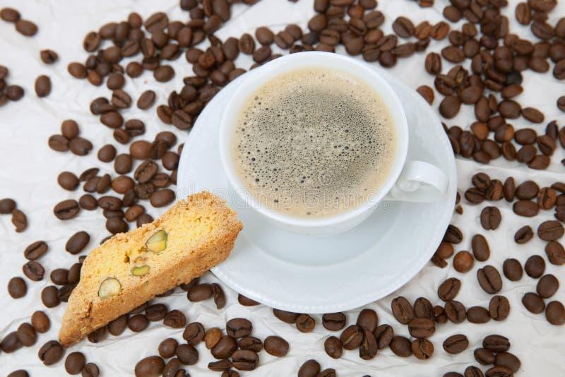 Η άσπρη κούπα του αμερικανικού καφέ με το κομμάτι του biscotti στοκ εικόνα