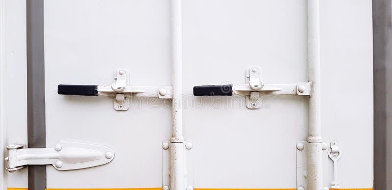 Η άσπρη πόρτα χάλυβα του εμπορευματοκιβωτίου φορτίου με τη μαύρη λαβή έκλεισε για την κράτηση του προτερήματος στοκ εικόνες
