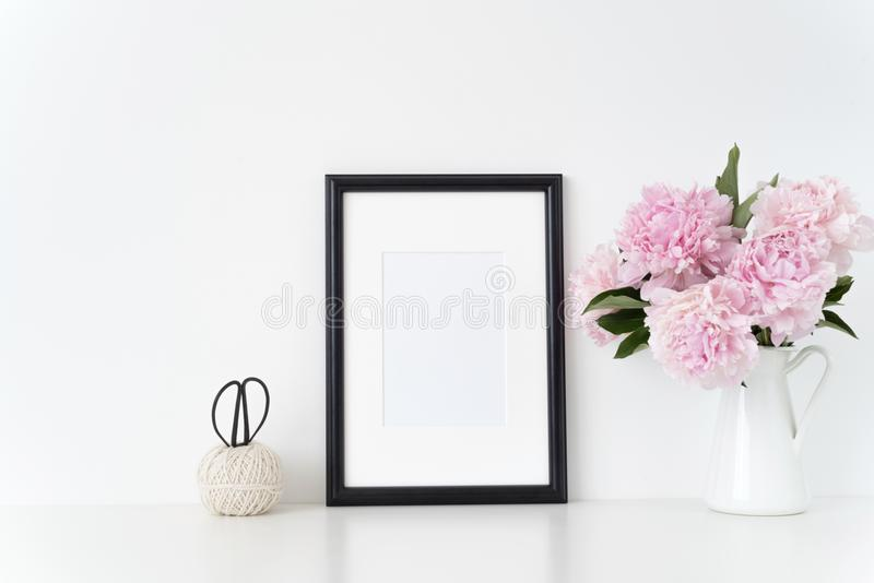 Η άσπρη χλεύη πλαισίων πορτρέτου επάνω με ρόδινα peonies εκτός από το πλαίσιο, επιστρώνει το απόσπασμα, την προώθηση, τον τίτλο,  στοκ εικόνα