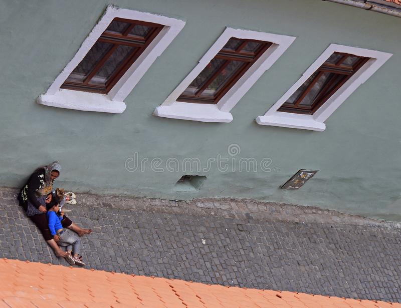 Η άστεγη, βρώμικη γυναίκα και ο γιος της στην άσφαλτο οδών στο Sibiu, Ρουμανία στοκ εικόνα με δικαίωμα ελεύθερης χρήσης