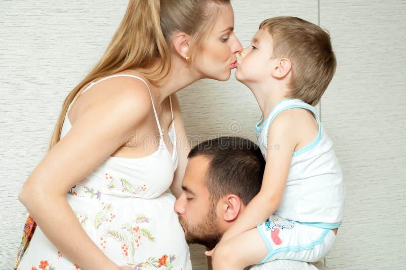 Η έγκυοι μητέρα, ο πατέρας και ο γιος φιλούν στοκ εικόνα