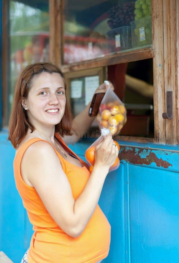 Η έγκυος γυναίκα αγοράζει τους καρπούς στοκ φωτογραφία με δικαίωμα ελεύθερης χρήσης