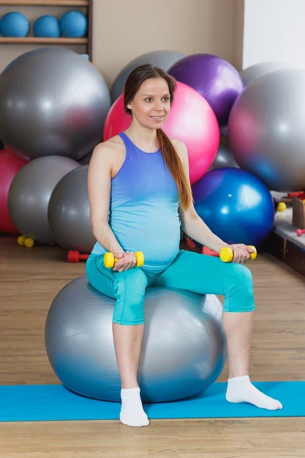 Η έγκυος γυναίκα κάνει την άσκηση στη σφαίρα με τους αλτήρες στοκ φωτογραφίες με δικαίωμα ελεύθερης χρήσης
