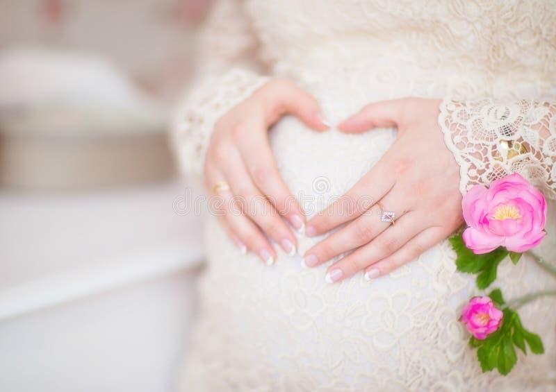 Η έγκυος γυναίκα που κρατά την παραδίδει μια μορφή καρδιών στην κοιλιά της στοκ εικόνες