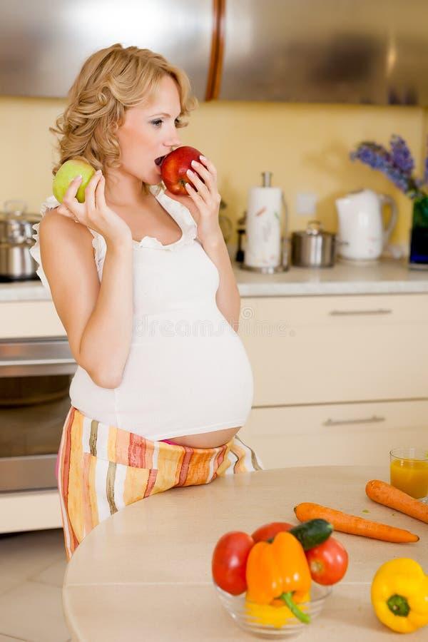 Η έγκυος γυναίκα τρώει το μήλο στοκ φωτογραφία