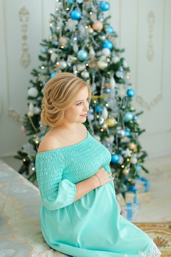 Η έγκυος ξανθή γυναίκα που φορά το μπλε φόρεμα που αγκαλιάζει την κοιλιά και που κάθεται κοντά στο χριστουγεννιάτικο δέντρο και π στοκ εικόνα με δικαίωμα ελεύθερης χρήσης