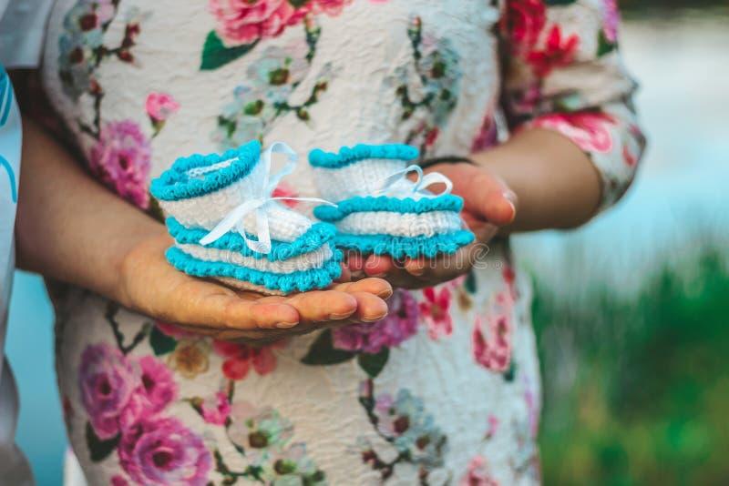 Η έγκυος σύζυγος και ο σύζυγός της κρατούν μπότες τις μικρές μωρών στενό σε επάνω χεριών τους στοκ εικόνες