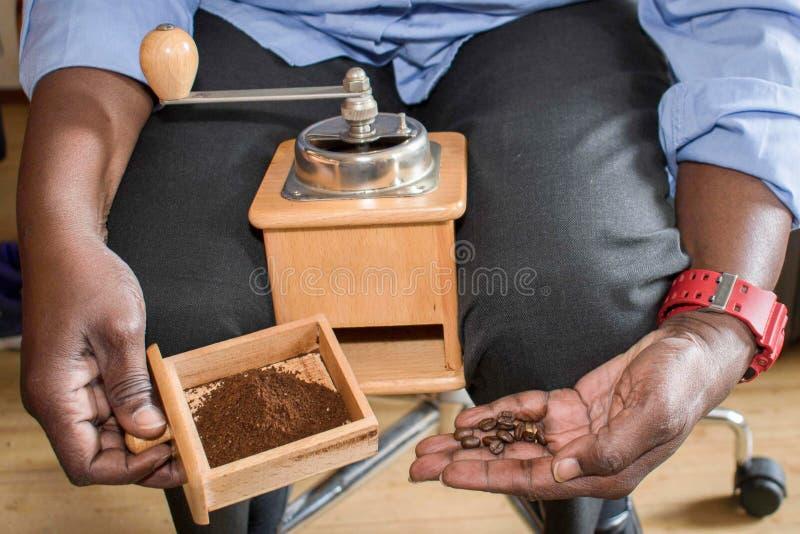 Η έγχρωμη γυναίκα αλέθει τον καφέ που παρουσιάζει το αποτέλεσμα στοκ εικόνες