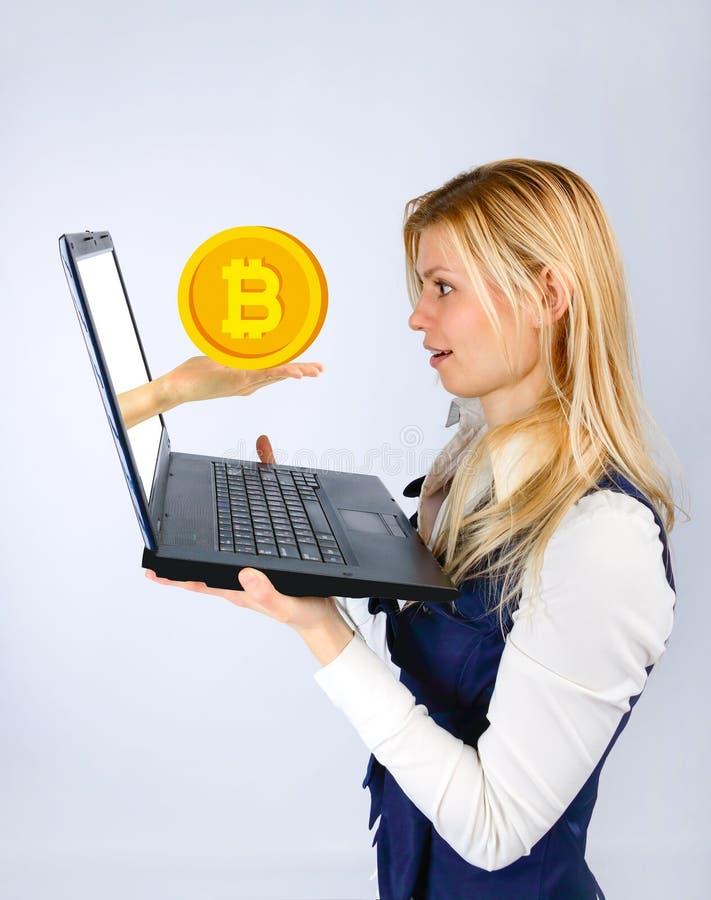 Η έκπληκτη γυναίκα κρατά ένα lap-top στα χέρια της, το χέρι από ένα lap-top προσφέρει bitcoin στοκ εικόνες