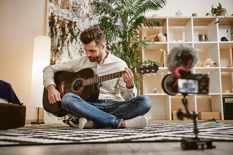 Η έμπνευσή μου Γενειοφόρος αρσενική συνεδρίαση μουσικής blogger στο πάτωμα και εκμετάλλευση η κιθάρα, καταγράφοντας το νέο βίντεο στοκ εικόνες