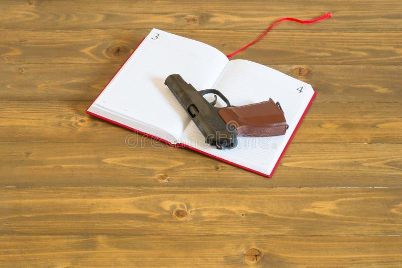 Η έννοια ενός κόκκινου βιβλίου και ενός πυροβόλου όπλου, το πρόβλημα των όπλων στα σχολεία στοκ εικόνες με δικαίωμα ελεύθερης χρήσης