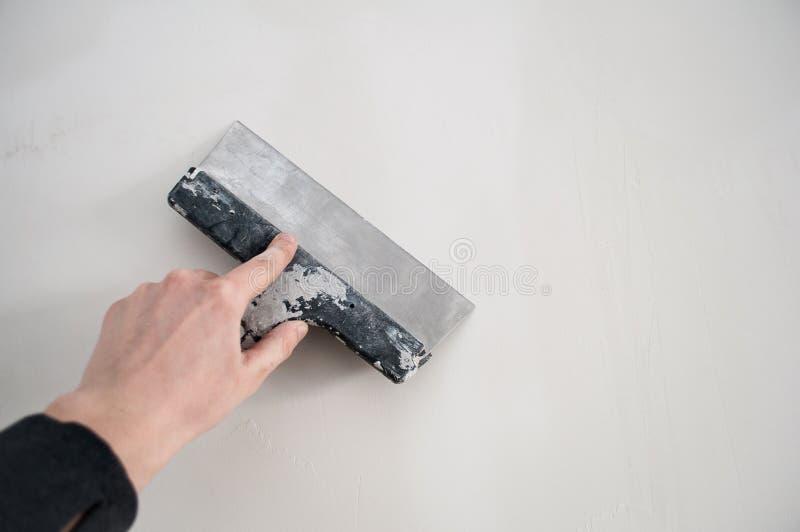 Η έννοια επισκευής, εργαλεία επισκευής, χέρι κρατά spatula κατασκευής ευθυγραμμίζει την εργασία τοίχων Ζωγραφική του τοίχου επισκ στοκ εικόνες