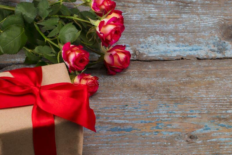 Η έννοια ημέρας βαλεντίνων με τα κόκκινα ροδαλά λουλούδια και το κιβώτιο δώρων επιζητά επάνω στοκ εικόνα