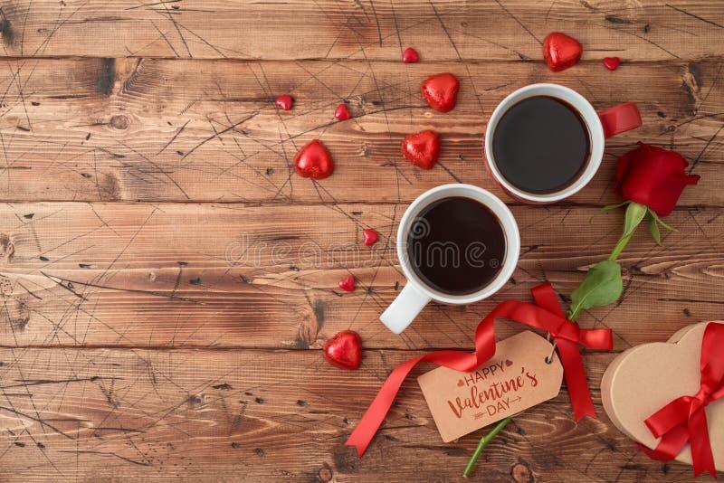 Η έννοια ημέρας του βαλεντίνου με τα φλυτζάνια καφέ, σοκολάτα μορφής καρδιών, αυξήθηκε λουλούδι και κιβώτιο δώρων στοκ φωτογραφίες